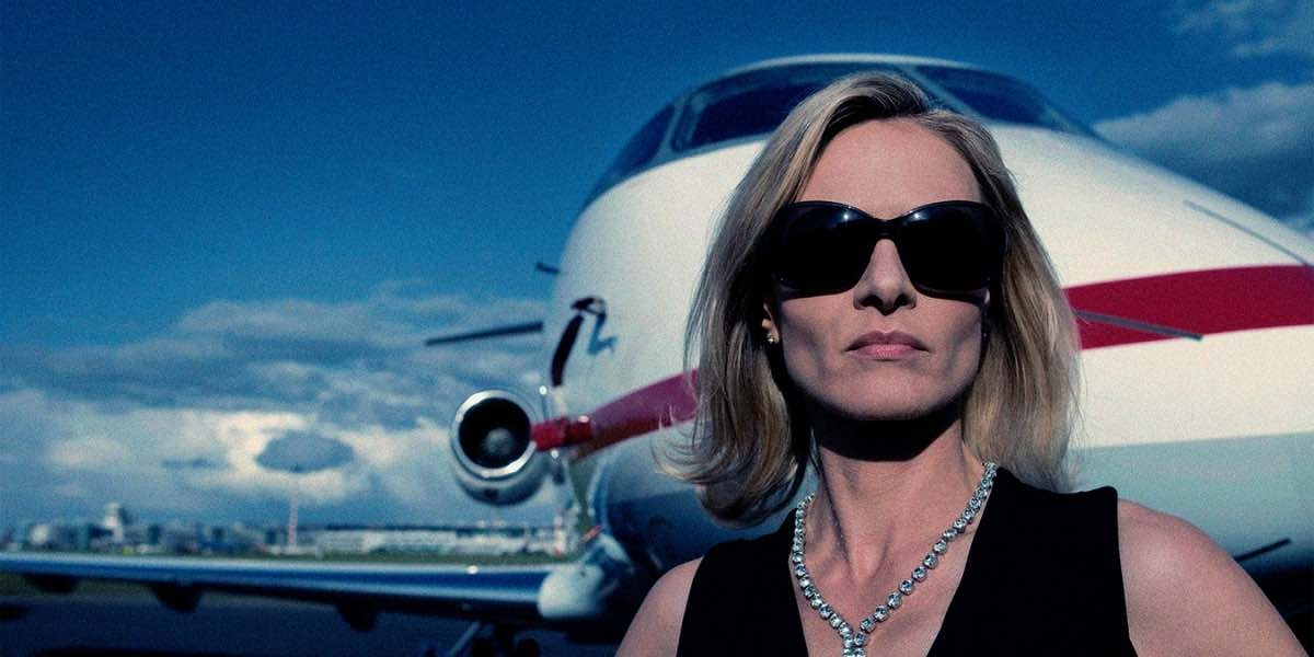 Rich blond woman in sunglasses and diamond necklace in front of a private jet.
